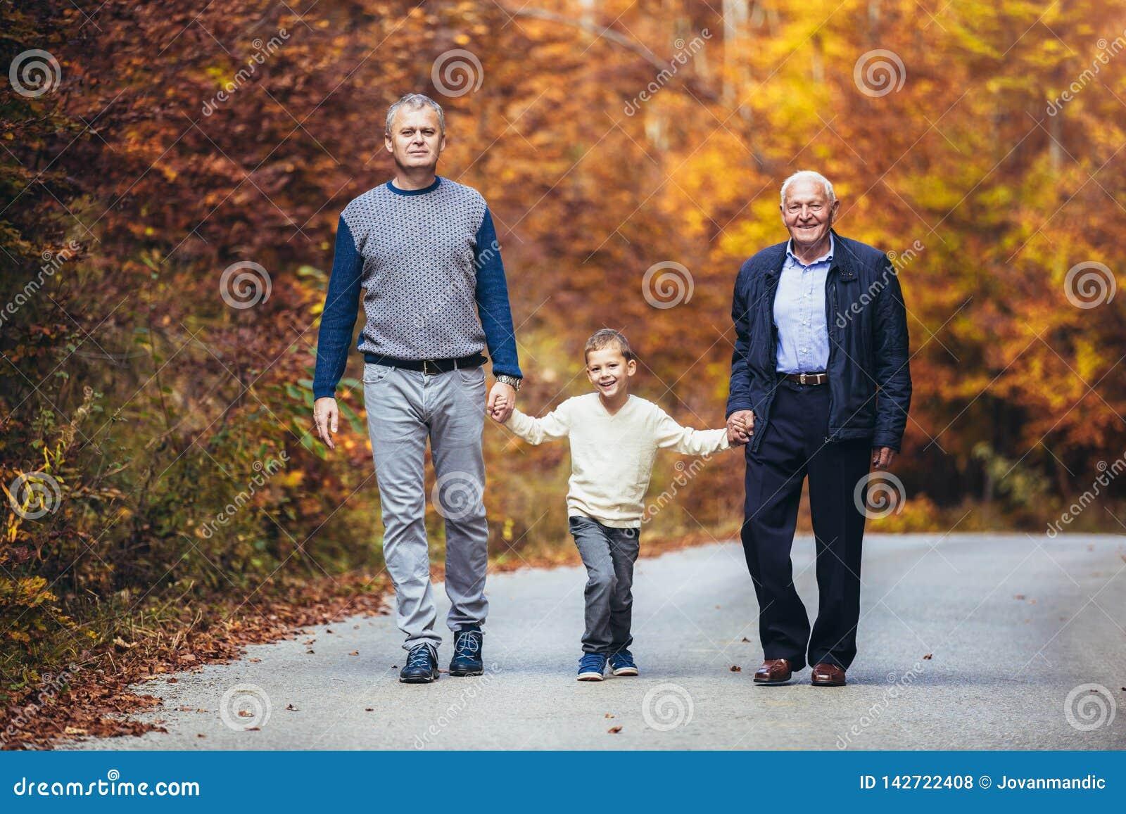 Сын и внук пожилого отца взрослый вне для прогулки в парке