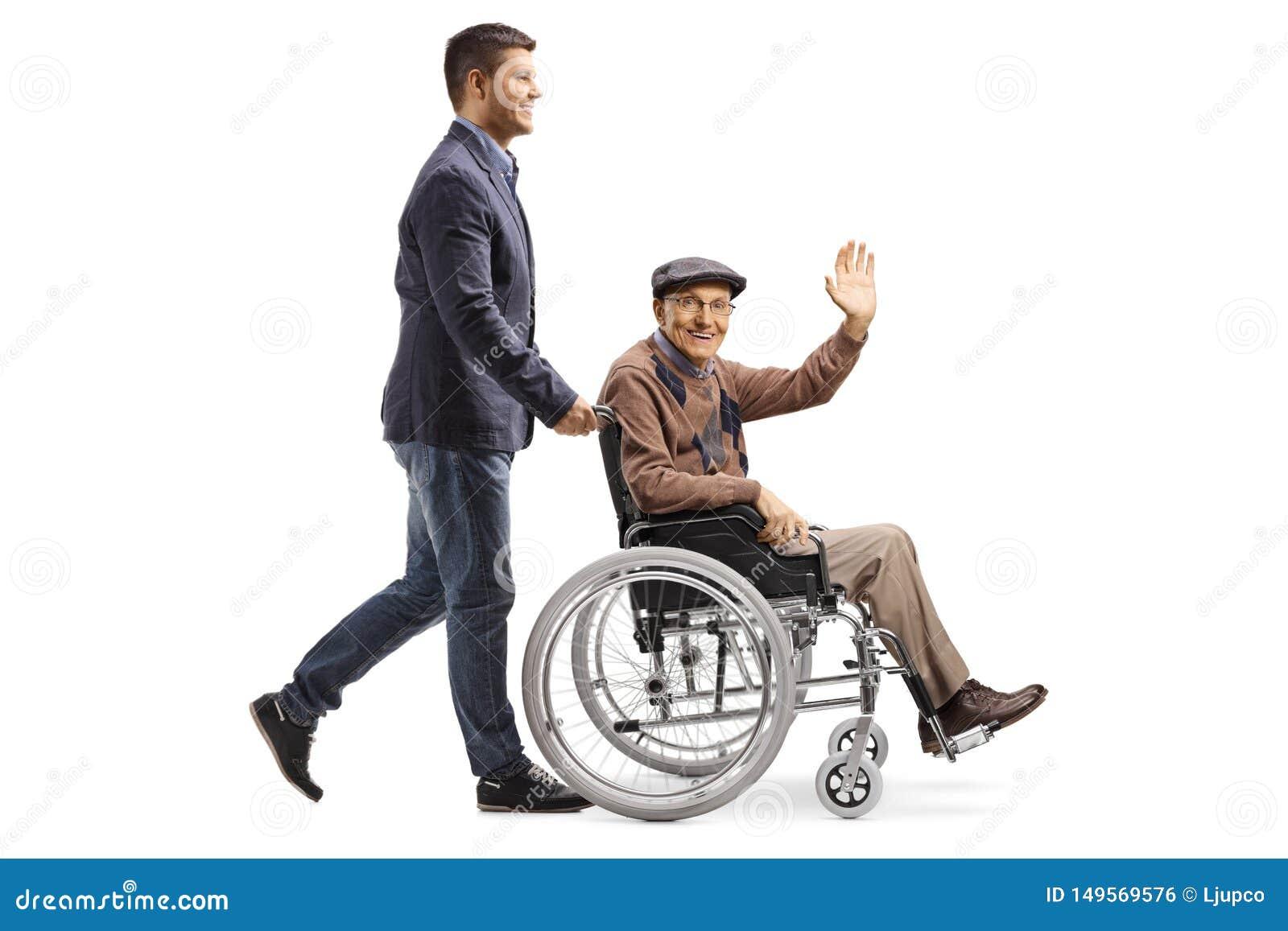 Сын нажимая его отца развевая от кресло-коляскы