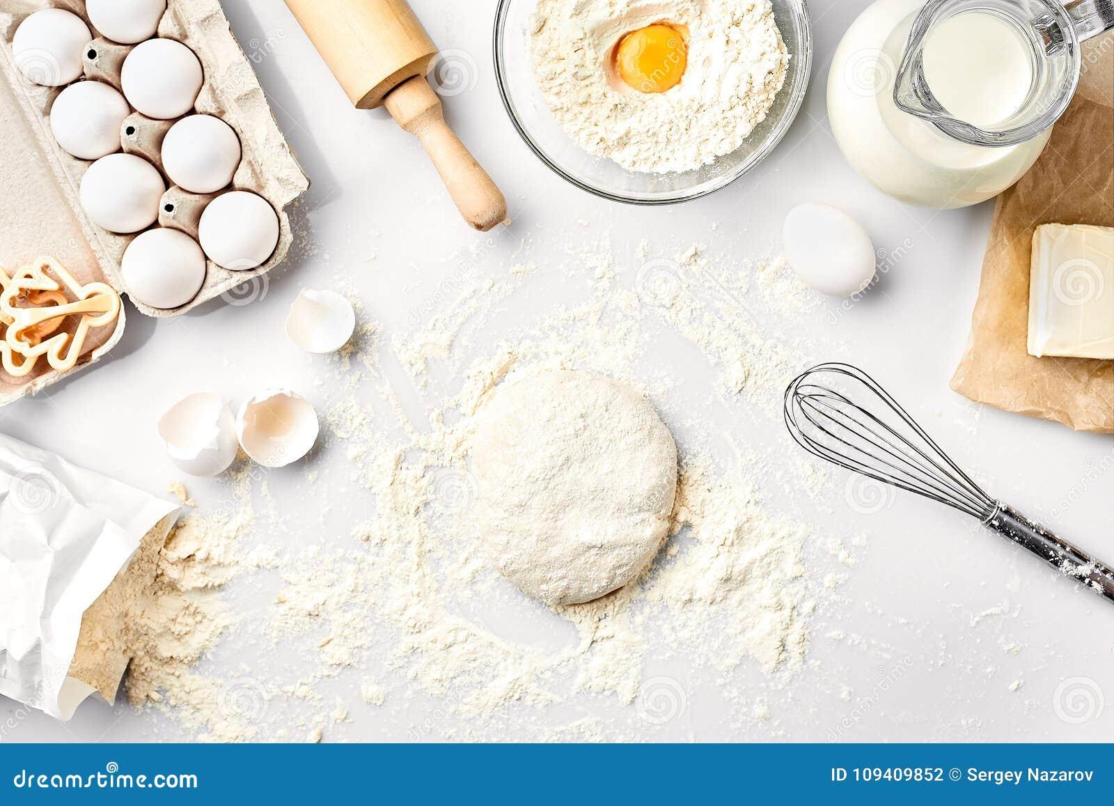 Сырцовое тесто готовое для замешивать на белой таблице Ингридиенты хлебопекарни, яичка, мука, масло Формы для делать печенья