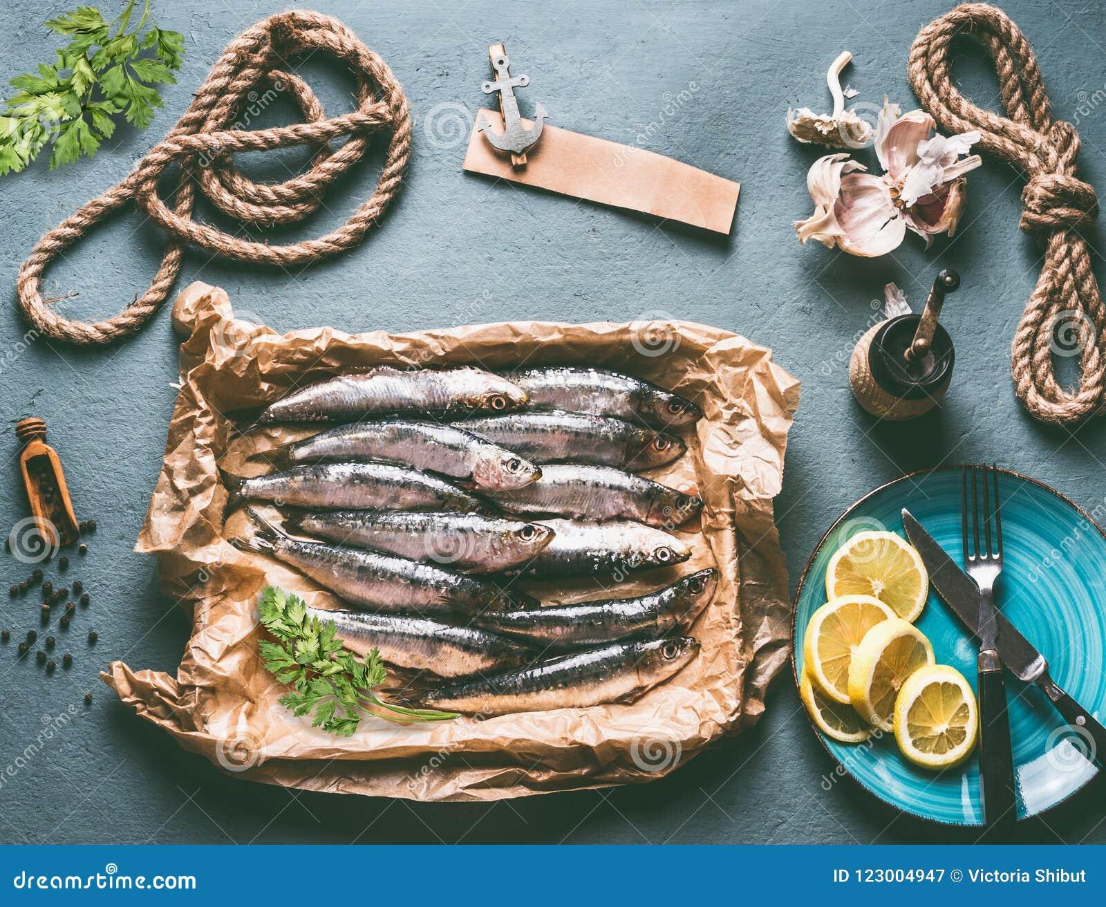 Сырцовые сардины на предпосылке кухонного стола с ингридиентами лимон, чеснок и травы для вкусный варить морепродуктов