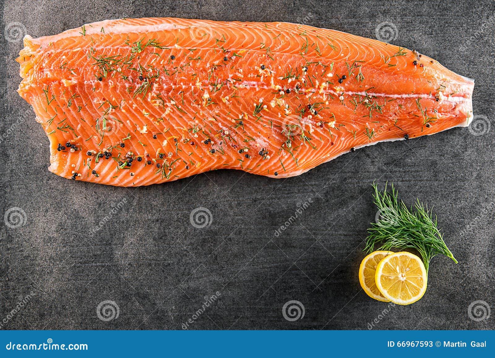 Сырцовый salmon стейк рыб с лимоном и укропом на черной доске, современной гастрономии в ресторане