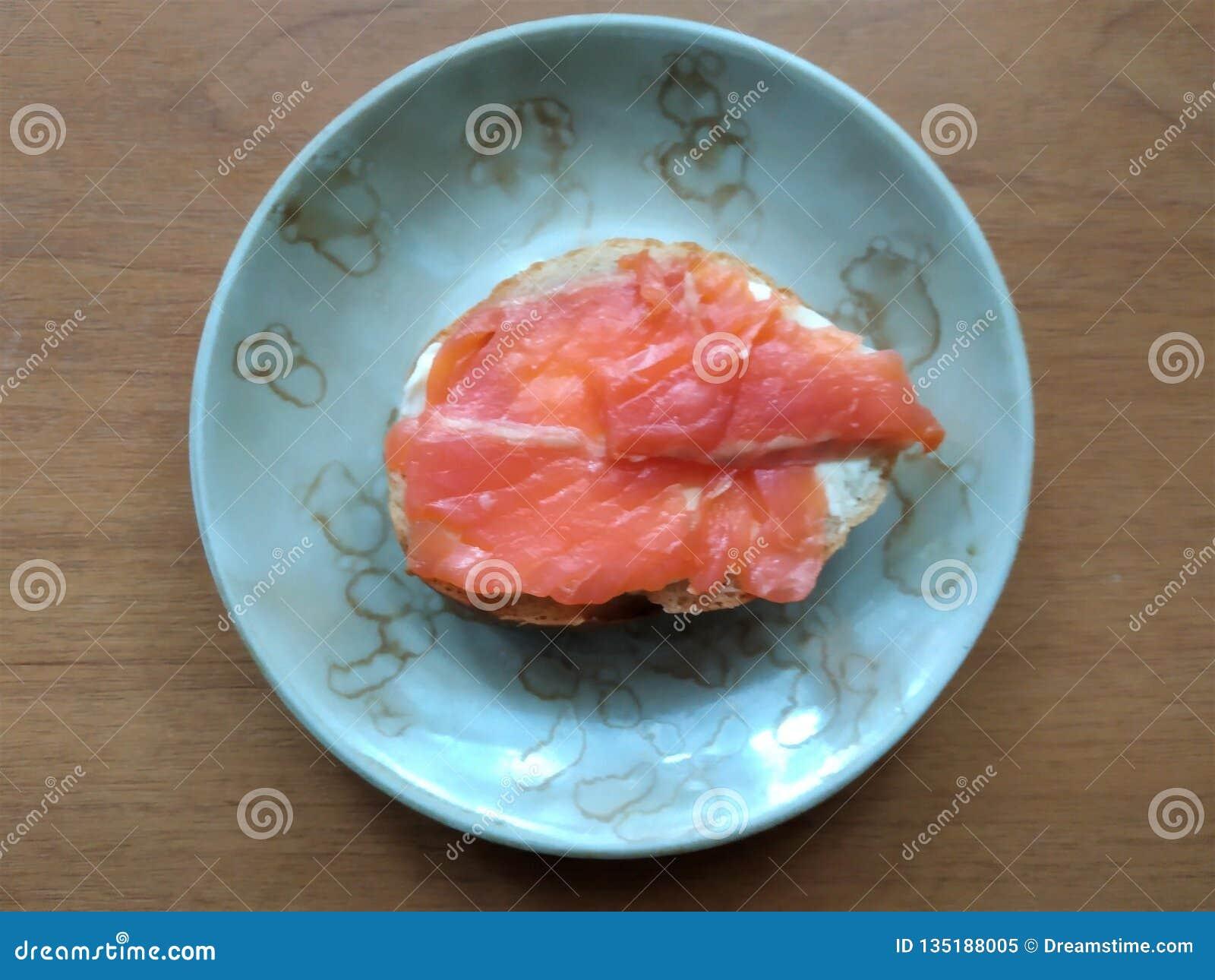Сэндвич с частями красных рыб на белом хлебце смазанном с маслом, завтраке, закуске