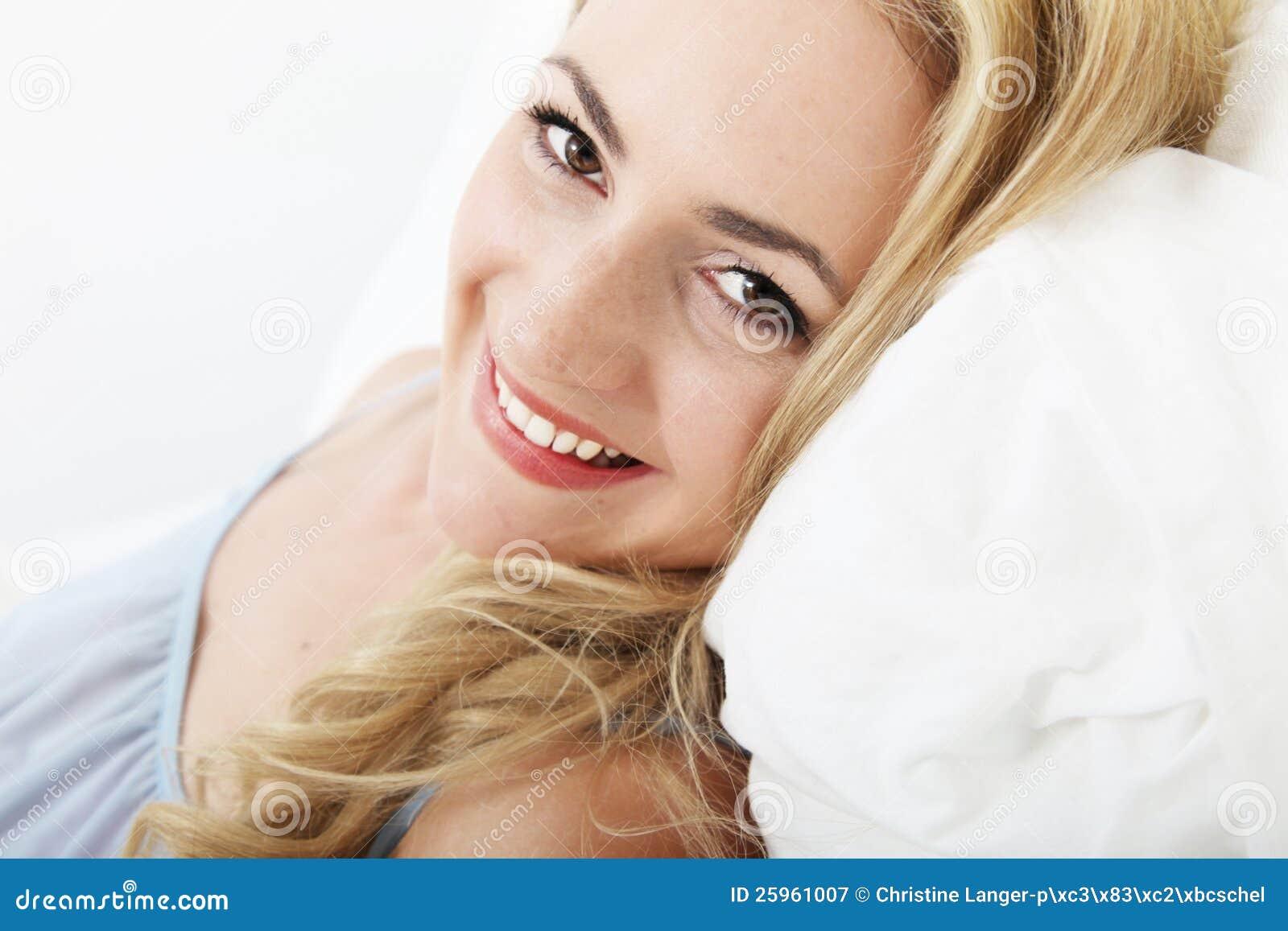 Ся счастливая женщина ослабляя в кровати