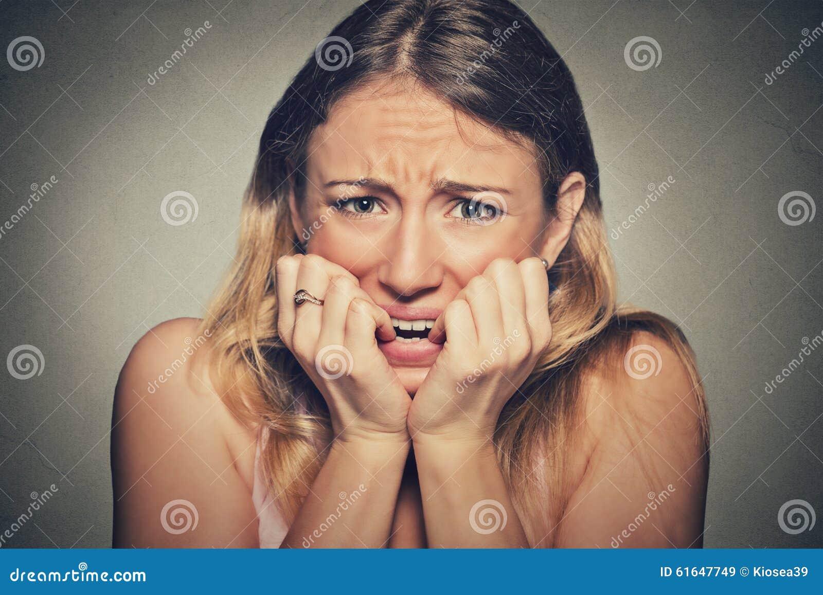 Слабонервные усиленные ногти молодой женщины сдерживая смотря тревожено жаждающ