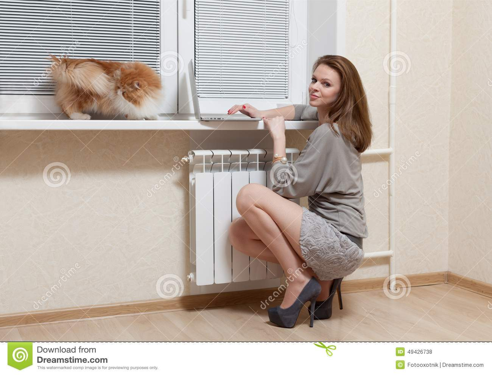 Славная блондинка на окне с компьтер-книжкой