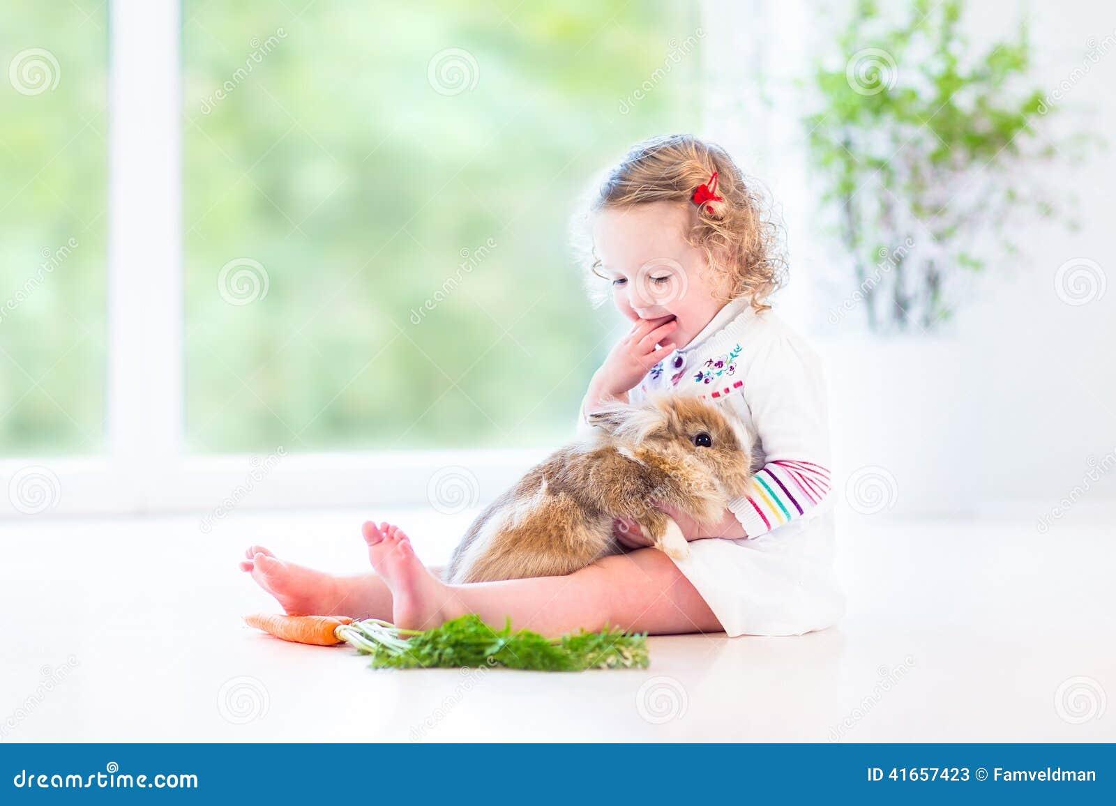 Сладостная девушка малыша с вьющиеся волосы с реальным зайчиком