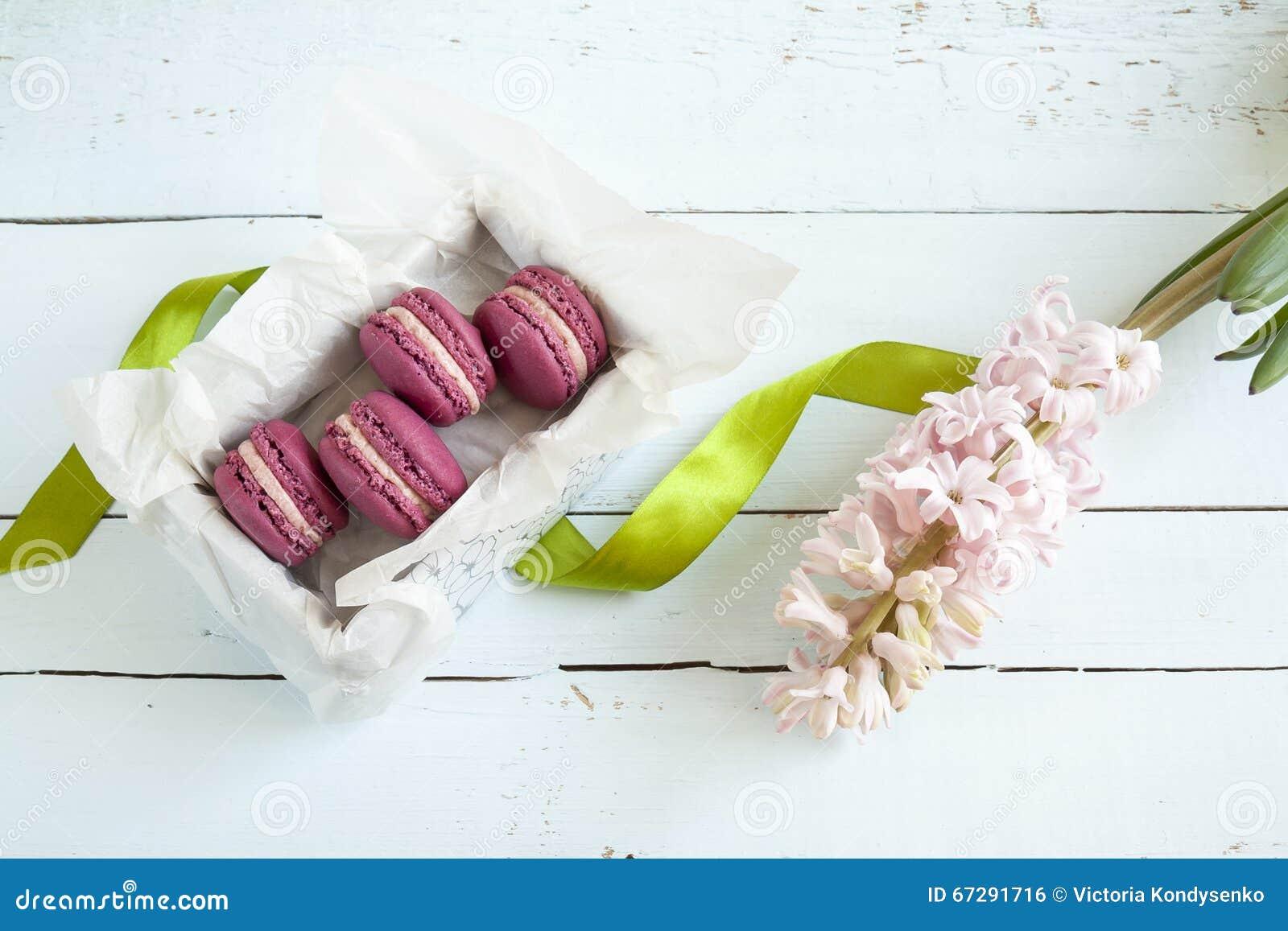 Сладостные малиновые французские macaroons с коробкой и гиацинтом на свете покрасили деревянную предпосылку