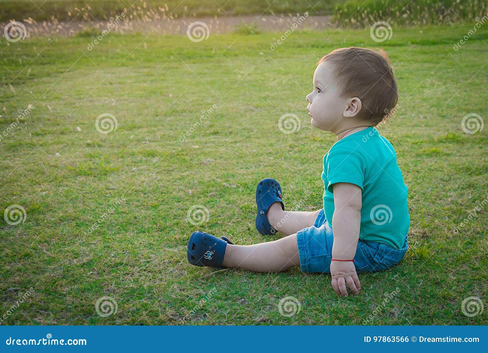 Сладостный ребёнок сидя в парке осени