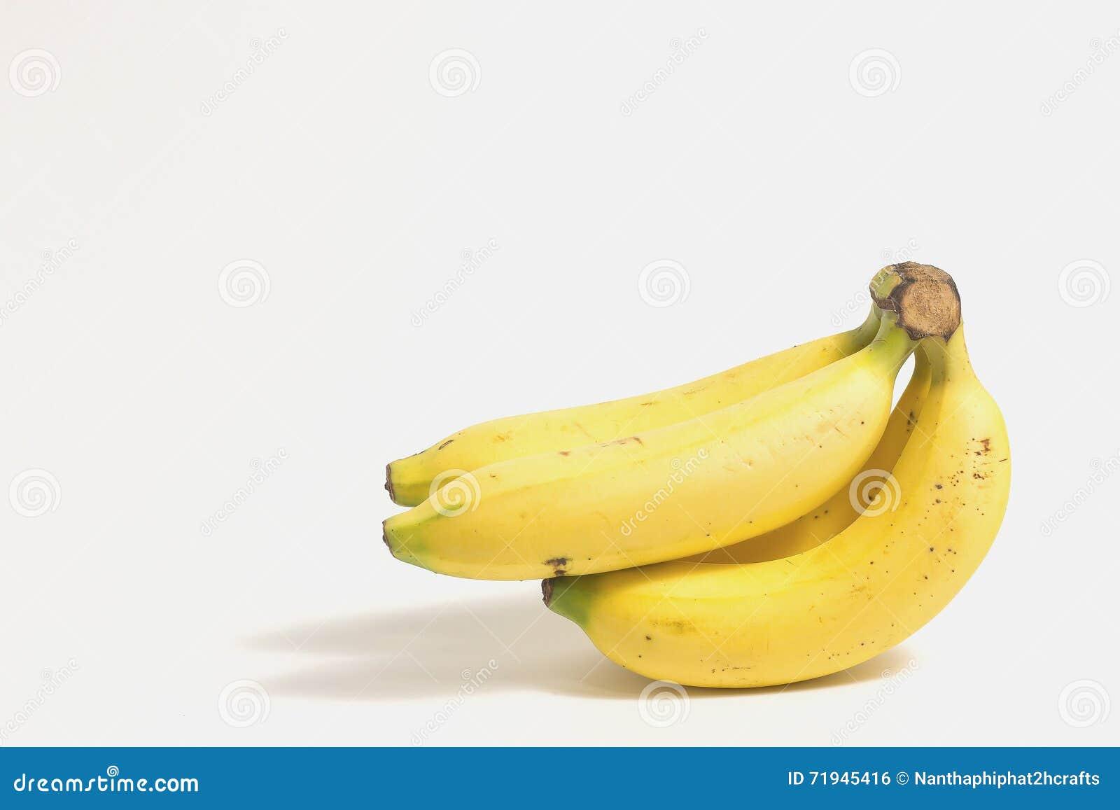 Слезли банан около группы зрелых бананов на белой предпосылке