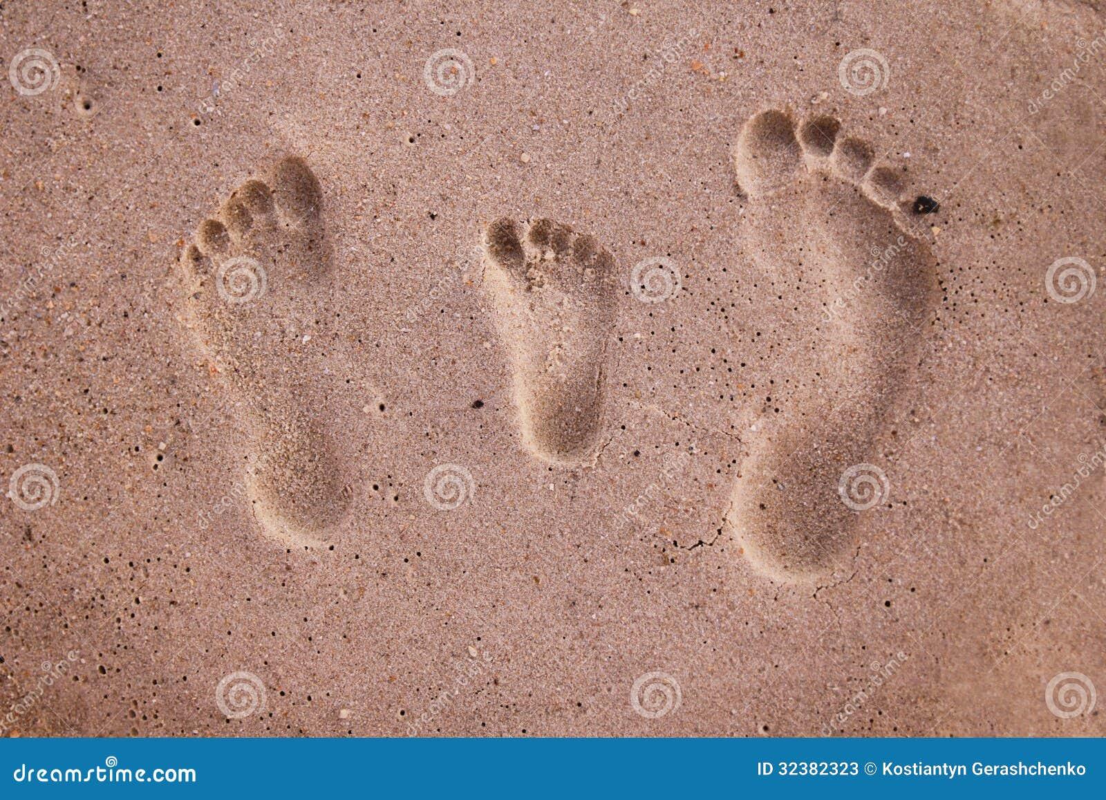 Следы ноги семьи в песке на пляже