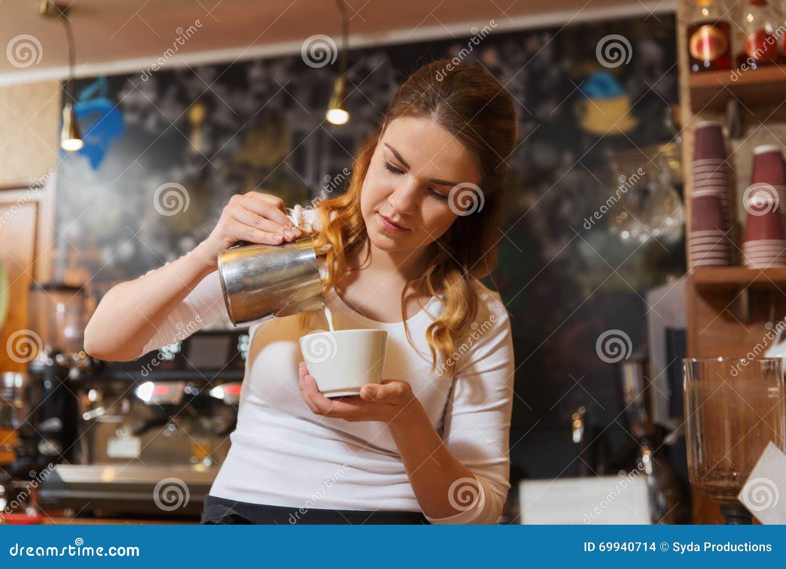 Сливк женщины Barista лить, который нужно придать форму чашки на кофейне