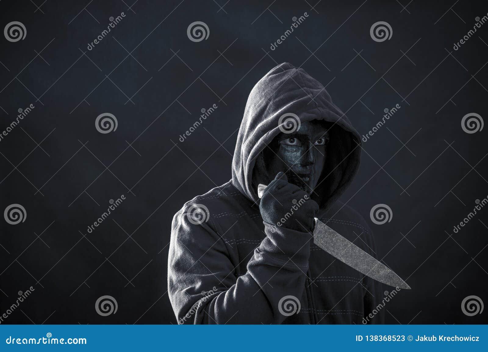 С капюшоном человек с черным ножом удерживания маски