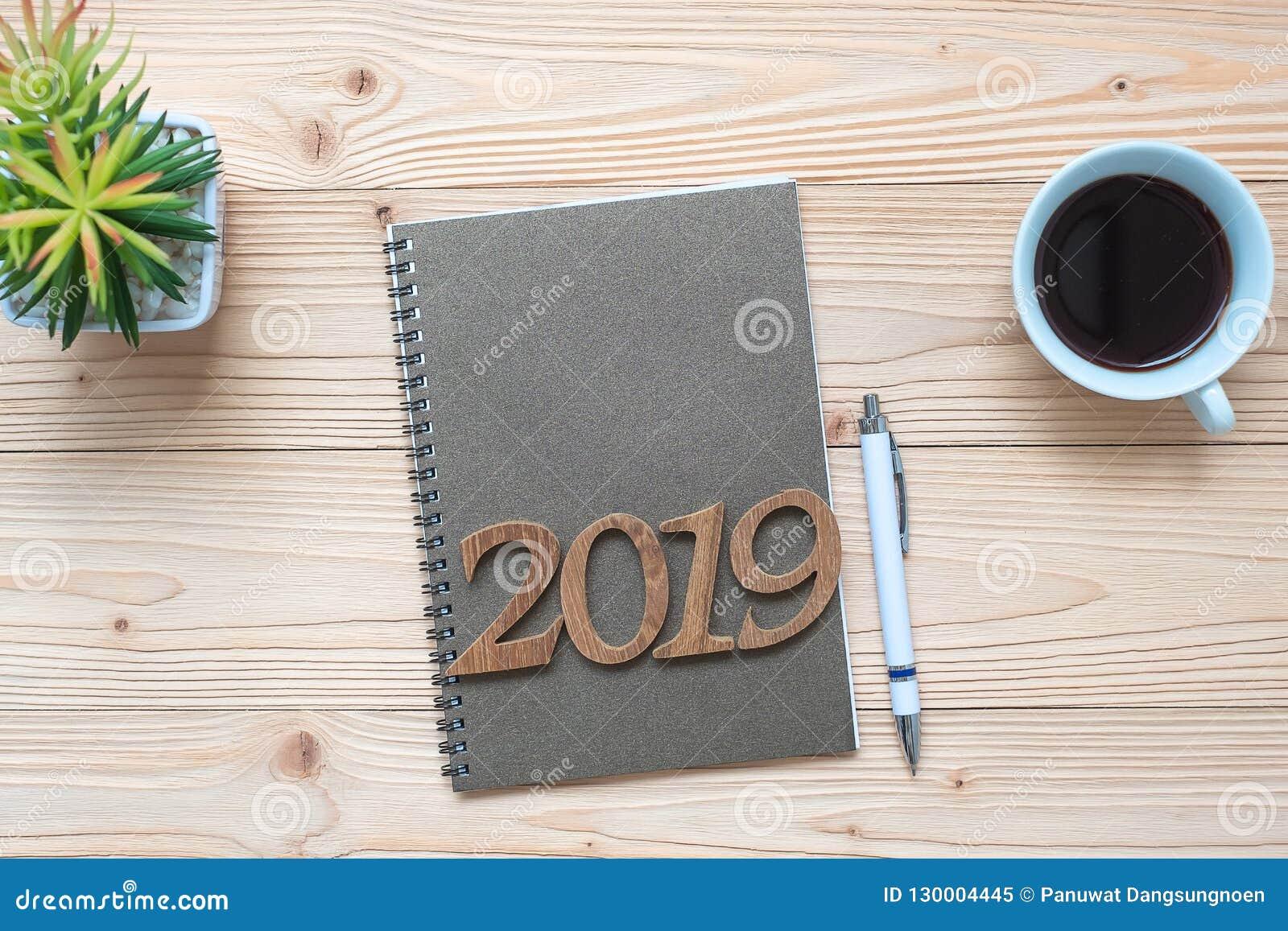 2019 С Новым Годом! с тетрадью, черной кофейной чашкой, ручкой и стеклами на деревянном столе, космосе взгляда сверху и экземпляр
