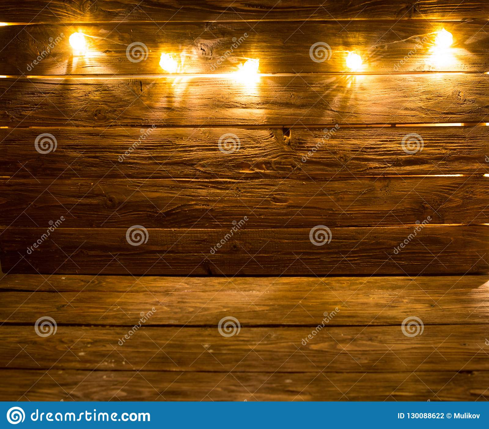 С Рождеством Христовым! Предпосылка света рождества на коричневой деревенской деревянной предпосылке