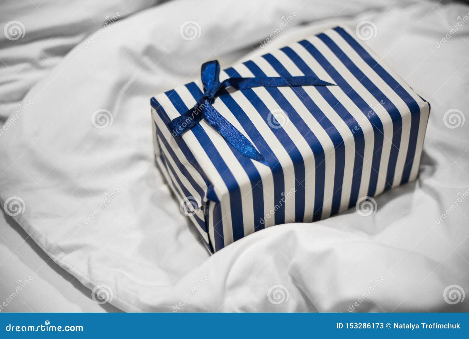 ?lose para arriba del regalo rayado azul para un hombre en una cama blanca Sorpresa de la ma?ana
