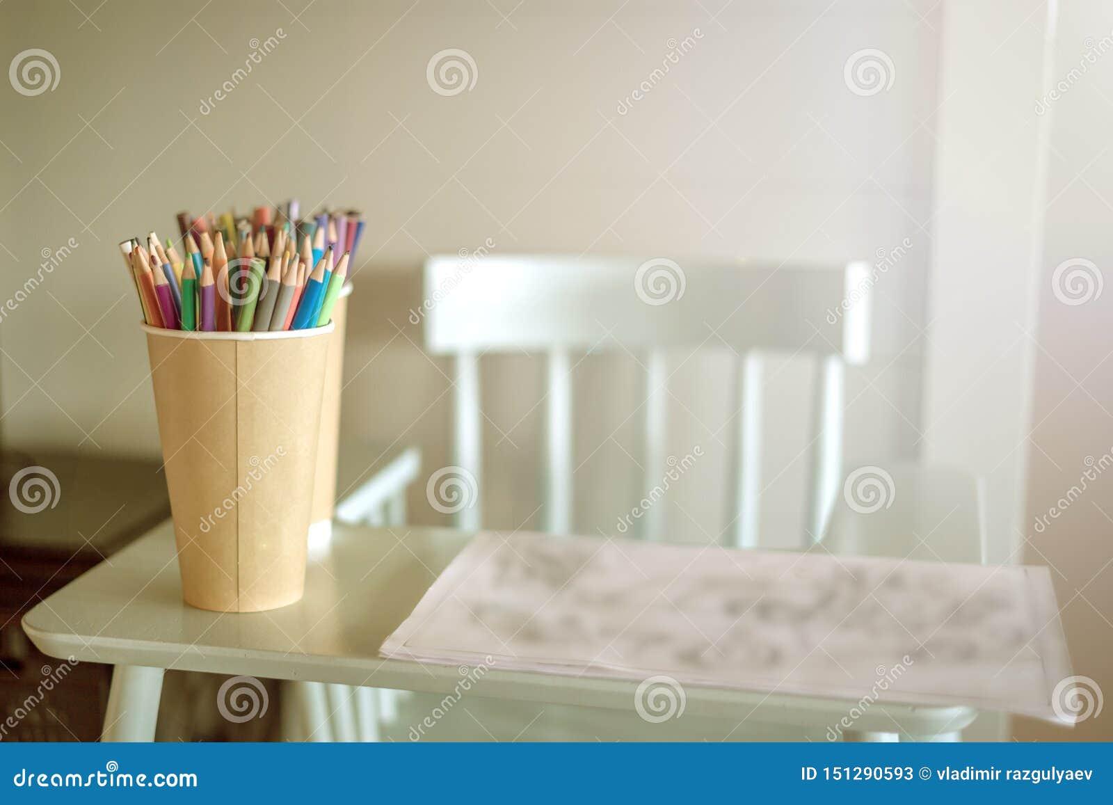 Сolored blyertspennor är på den höga stolen