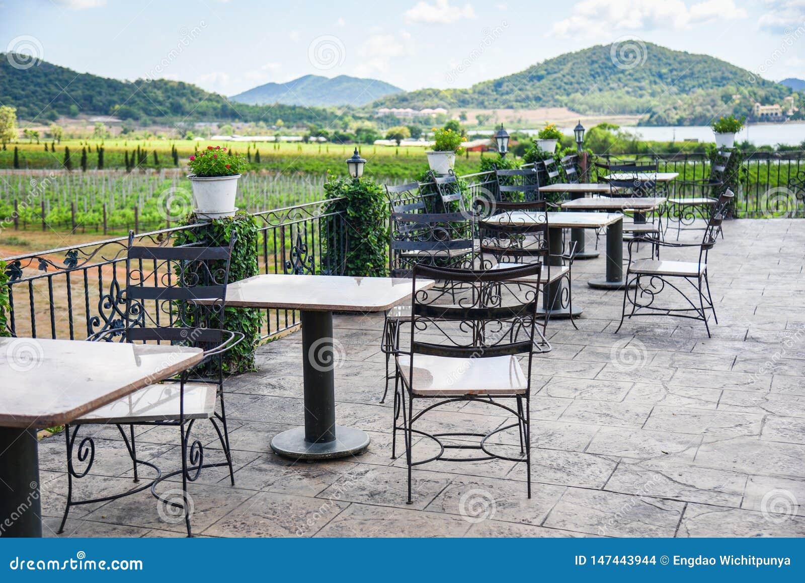 Таблица и стулья в балконе на открытом воздухе фермы природы взгляда ресторана и предпосылки горы - обеденного стола на террасе