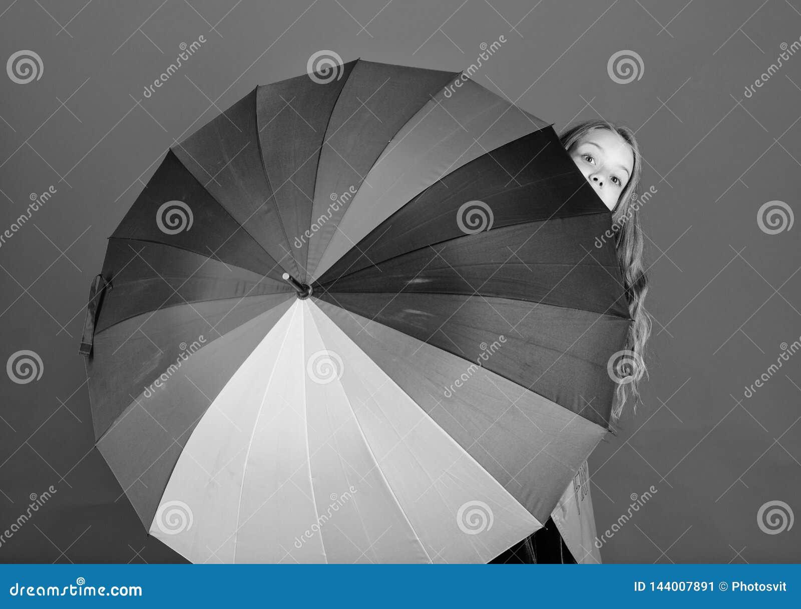 Тайник девушки жизнерадостный за зонтиком Красочный аксессуар зонтика Концепция прогноза погоды Дождливое пребывания положительно