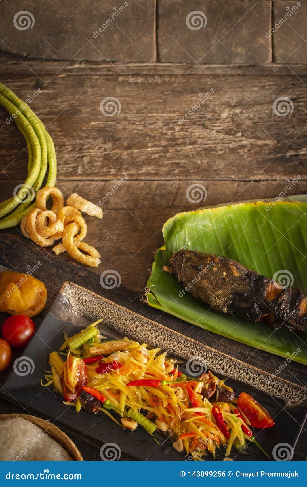 Тайцы животика сома салата папапайи на квадратной черной плите помещенной на деревянной таблице там длинная фасоль, сахар ладони,