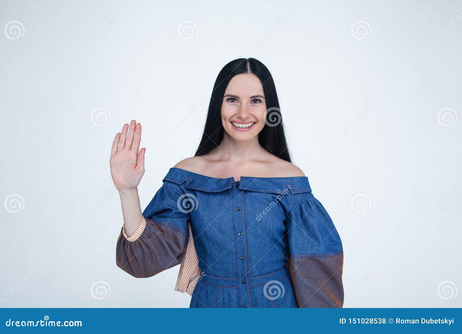 Талия вверх по портрету пойти молодая женщина брюнета с усмехаясь эмоцией показывая ее ладонь руки к камере одетый в джинсах оден