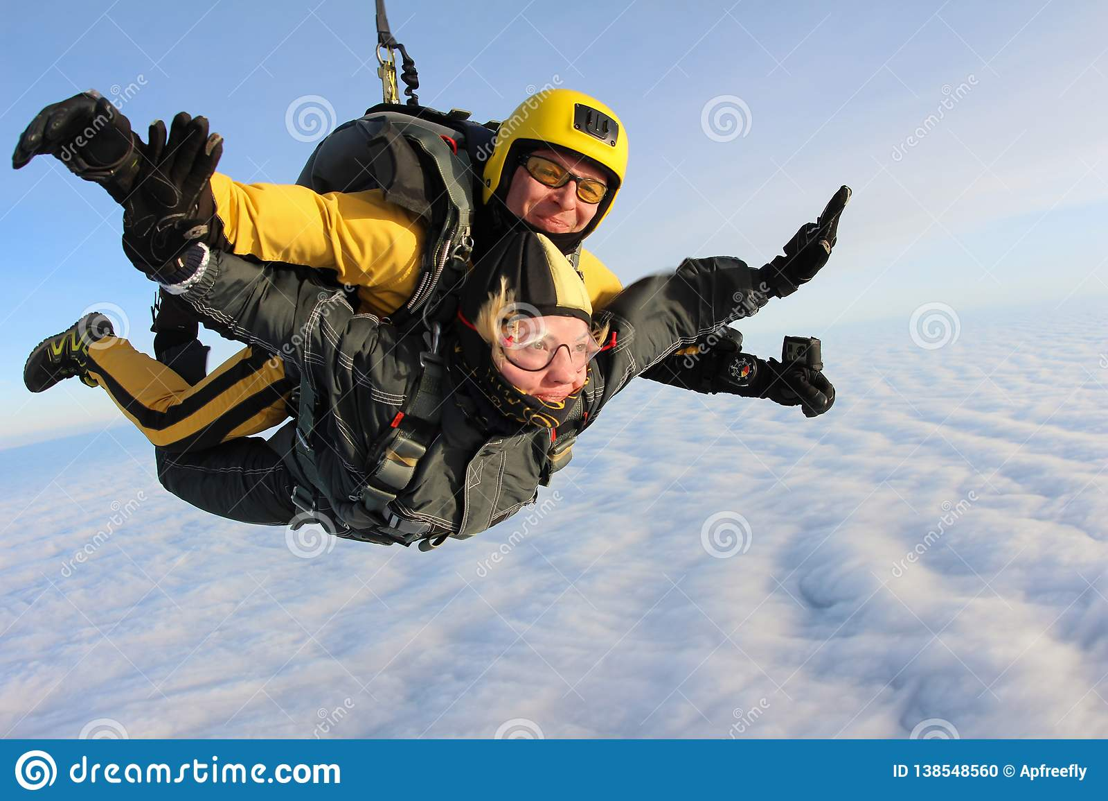 Тандемный skydiving Skydivers летают над белыми облаками