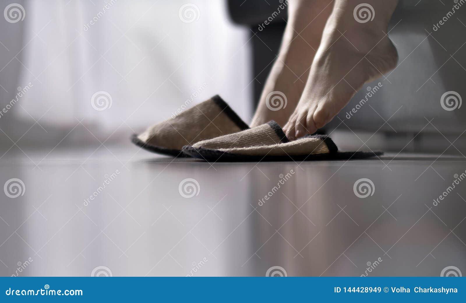Тапочки женщины нося получая вверх из кровати