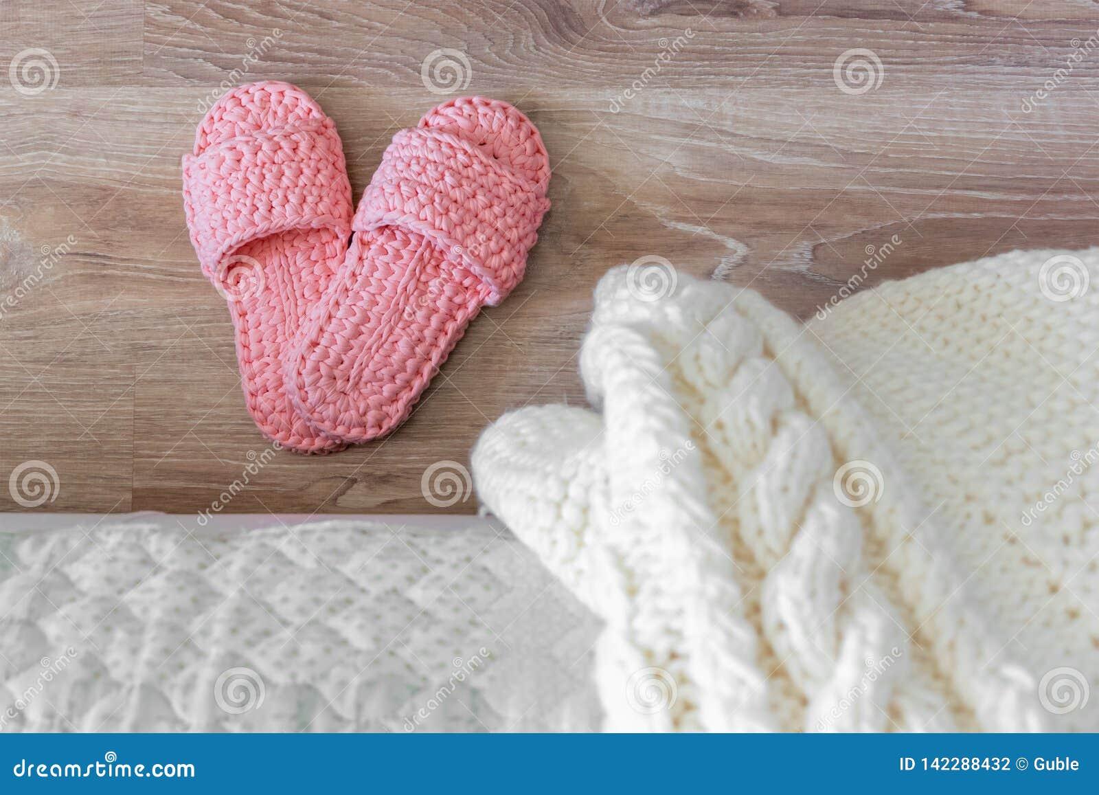 Тапочки связанного белого покрывала и розовых женщин около кровати