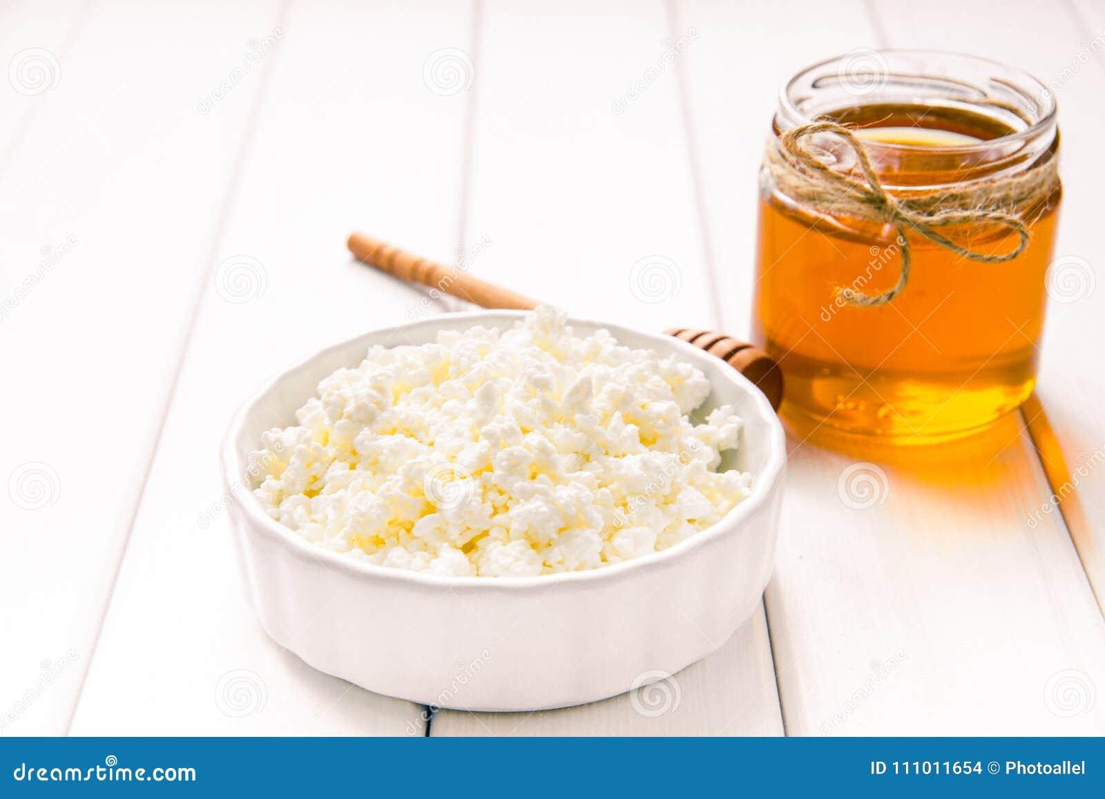 Творог молока с медом на белом деревянном столе Изображение селективного фокуса Copyspace для вашего текста