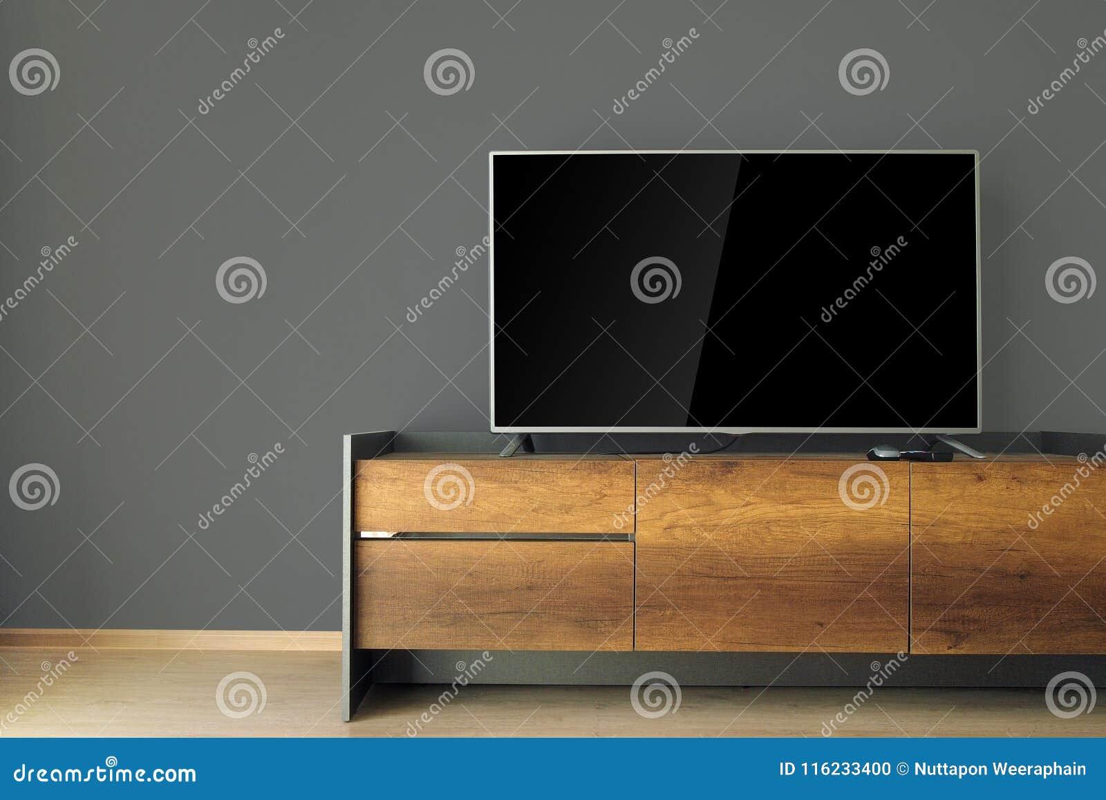 ТВ приведенное на стойке ТВ с черной стеной