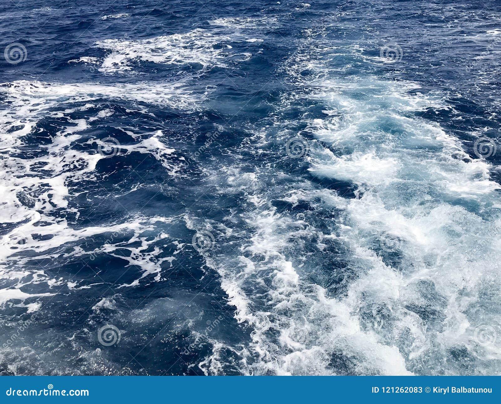 Текстура бурля голубой соленой воды моря с волнами, расслоины, пузыри, пена, трассировки после быстрой плавая тележки, шлюпки сно