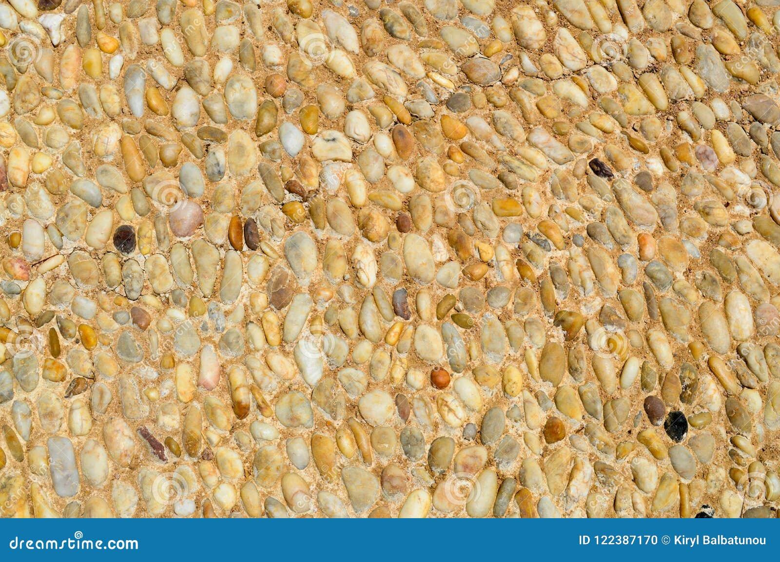 Текстура каменной стены, дорог от малого кругом и овальных камней с песком с швами естественного старого желтого черного коричнев