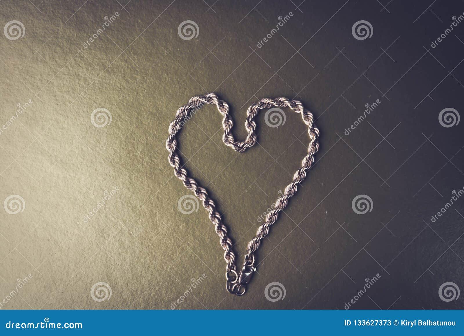 Текстура соткать красивой золотой праздничной цепи уникальный в форме сердца на черно-белом месте предпосылки и экземпляра