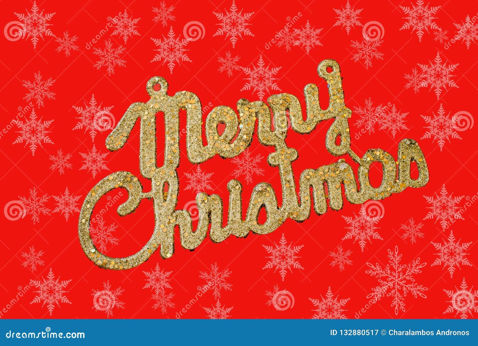 Текст веселого рождества золотой на красной предпосылке со снежинками