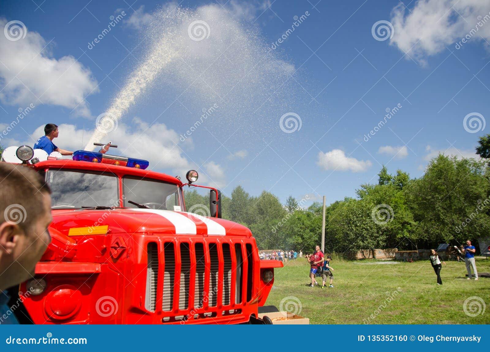 Тележка пожарного горящая льет воду от карамболя огня на радостных участниках в любительских конкуренциях
