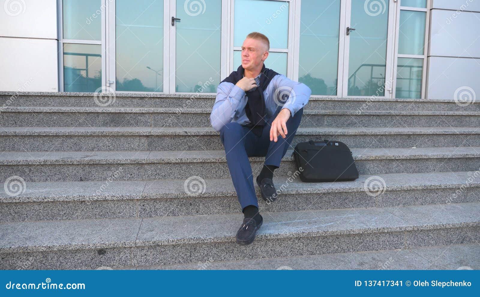 Тележка сняла отчаянного молодого бизнесмена сидя на лестницах около офисного здания и принимая кардиган  сток-видео