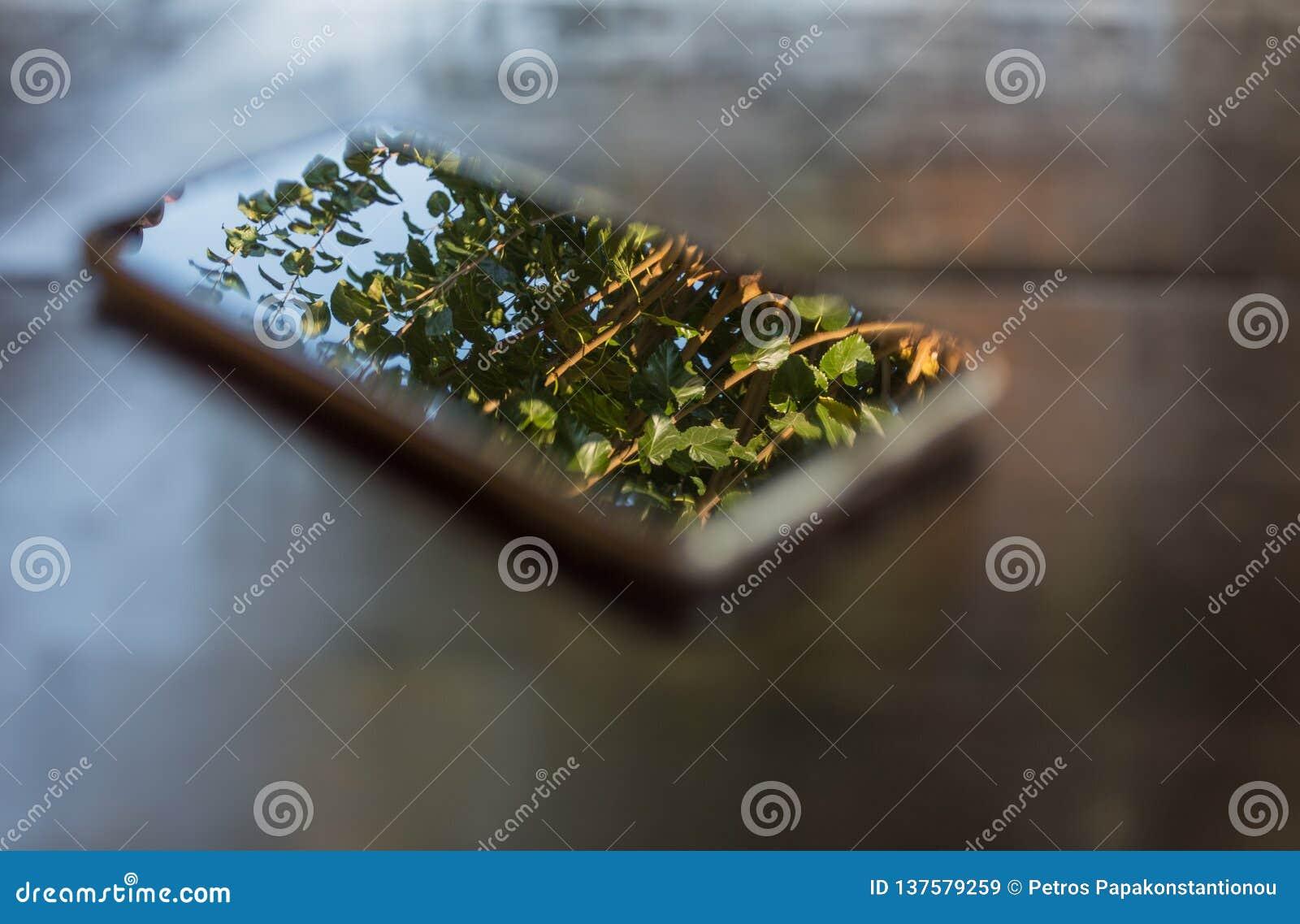 Телефон на экране деревянного стола в предпосылке фокуса художественной