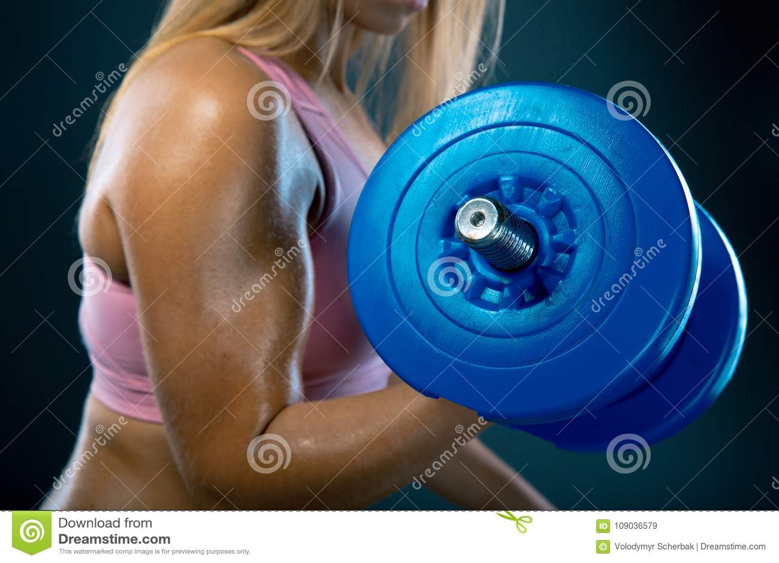 телохранителя Сильная женщина пригонки работая с гантелями Студия весов мышечной белокурой девушки поднимаясь сняла на темноте