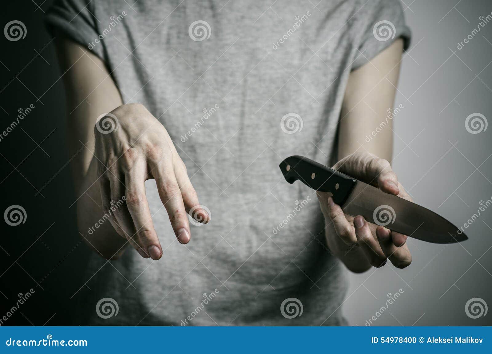 Тема убийства и хеллоуина: человек держа нож на серой предпосылке