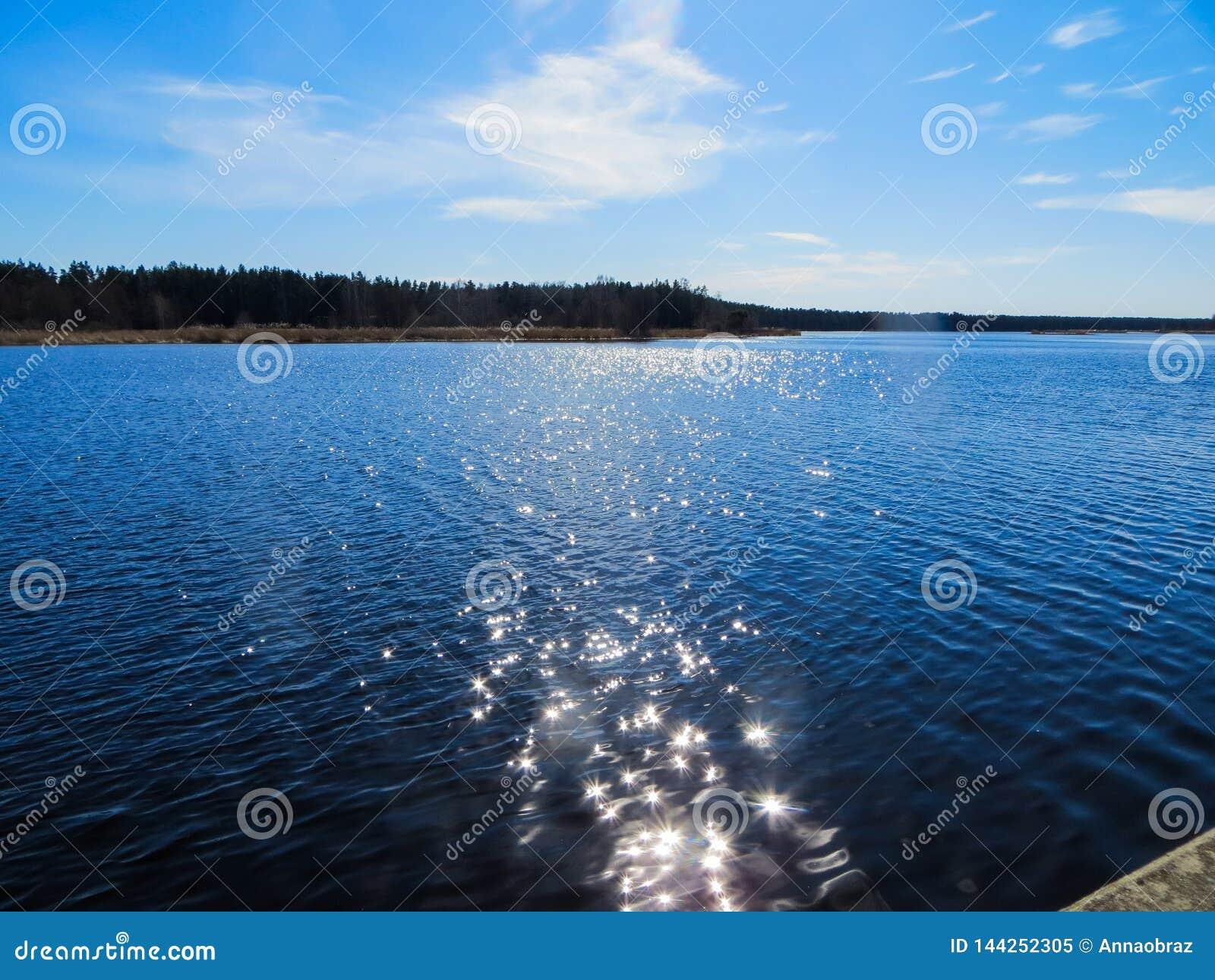 Темно-синая вода на реке Lielupe со слепимостью от яркого солнца в Латвии в предыдущей весне
