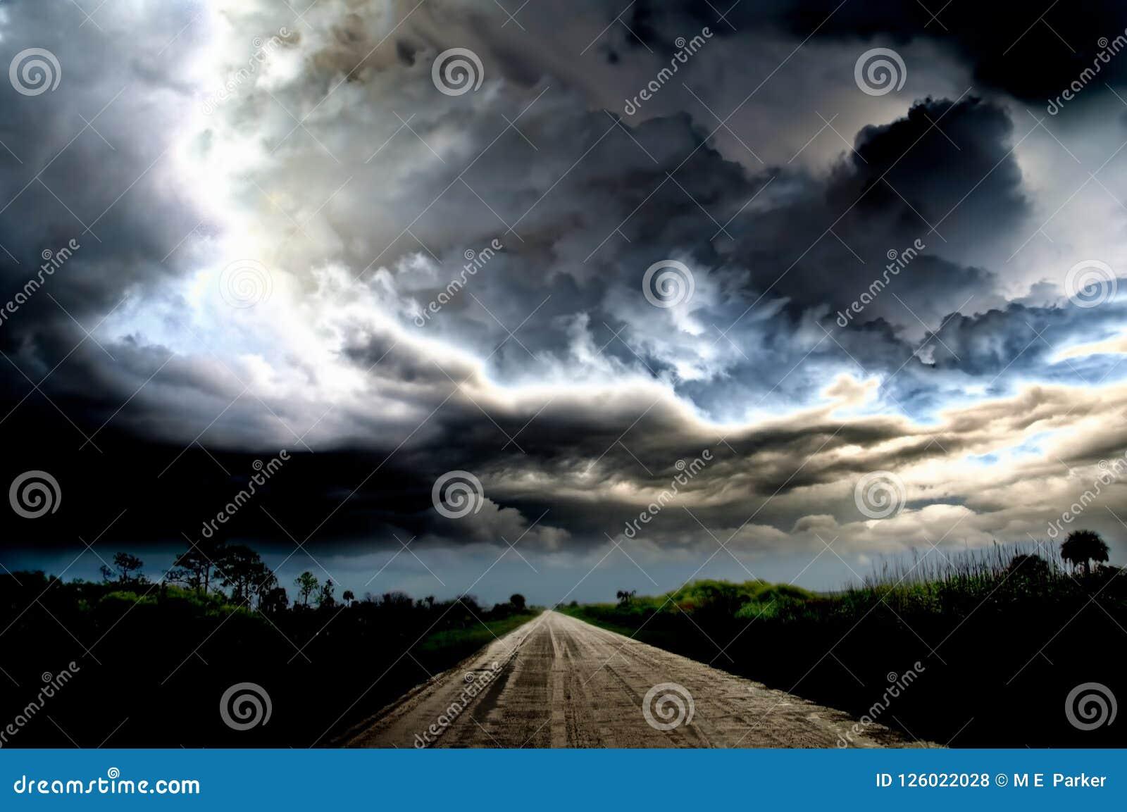 Темные облака грома и драматические штормы над сельской дорогой