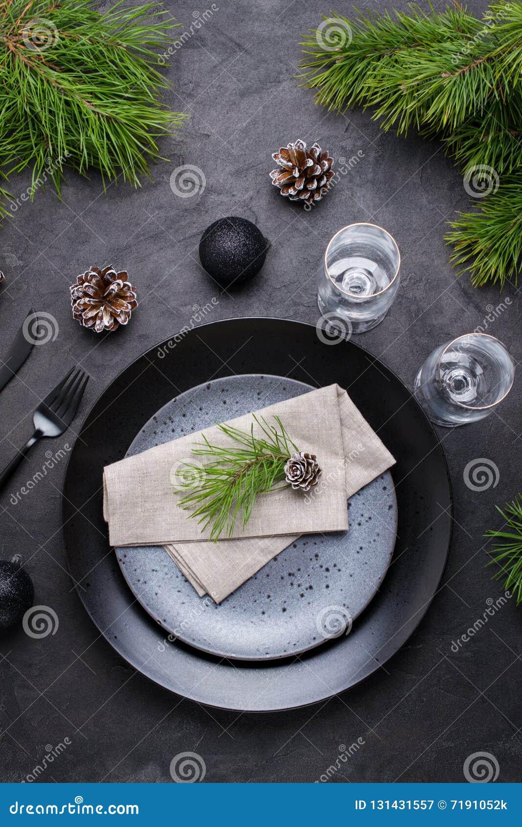 Темный дизайн сервировки стола рождества Черные плиты, стекла шампанского, вилка и набор ножа с салфеткой, ветвью ели