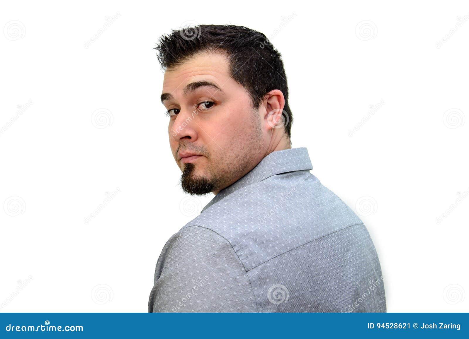 Темный с волосами человек в серой рубашке смотря назад на белом фоне