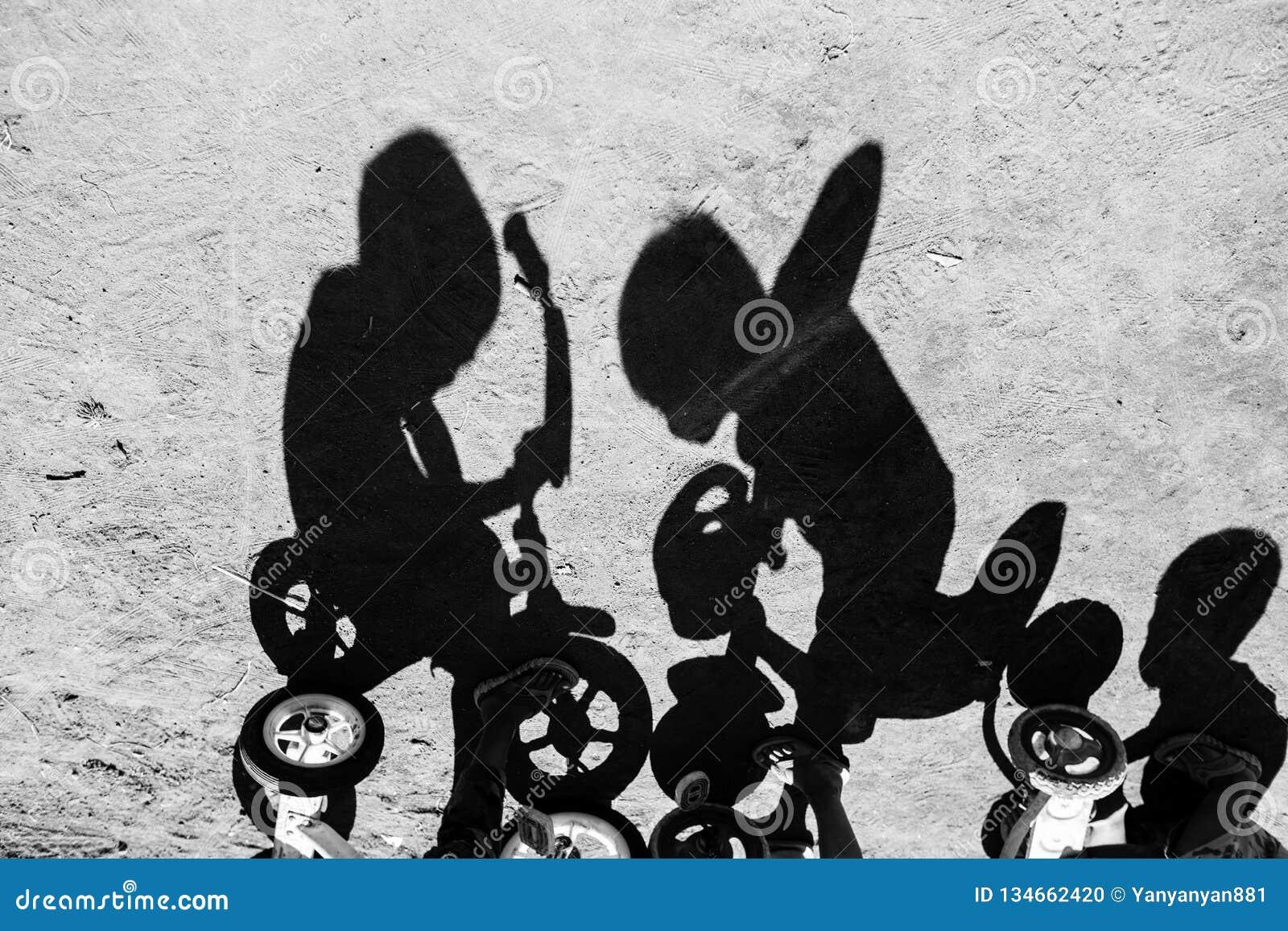 Тень детей ехать велосипед в деревне Бали Индонезии