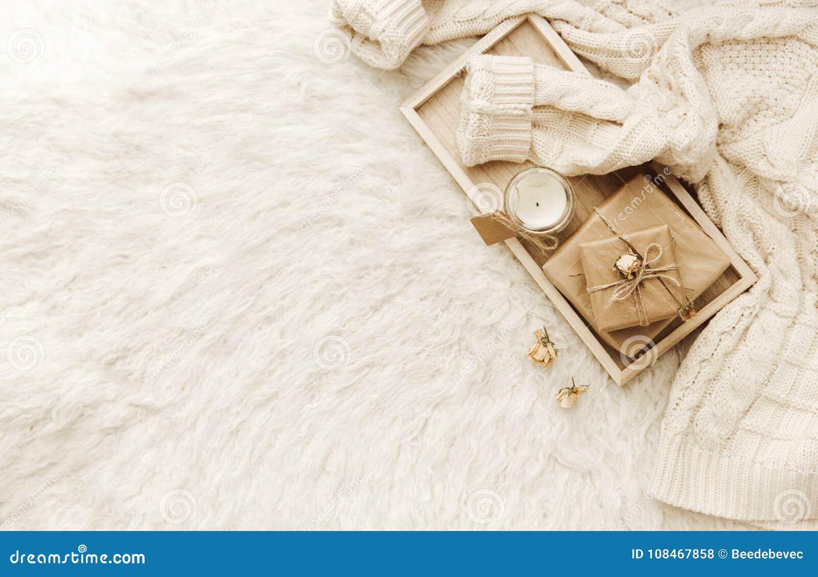 Теплый свитер, высушенные цветки на белой предпосылке