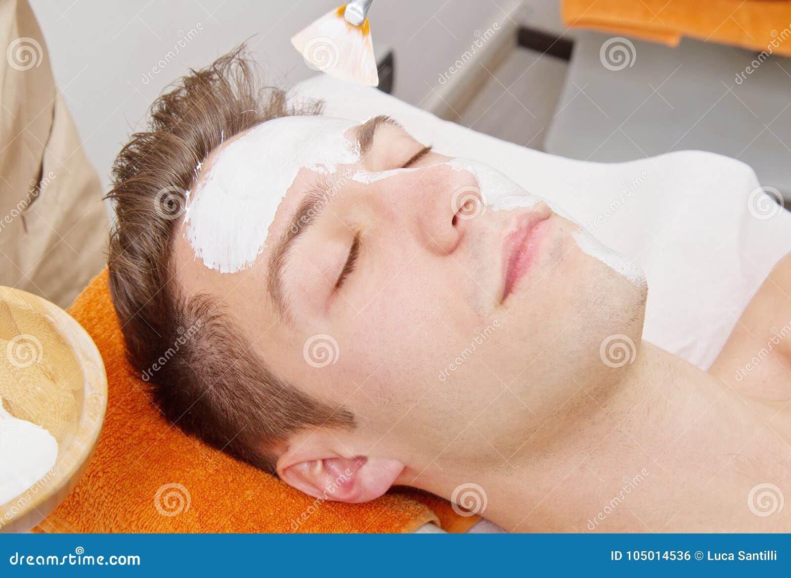 Терапевт прикладывая лицевой щиток гермошлема к красивому молодому человеку в курорте