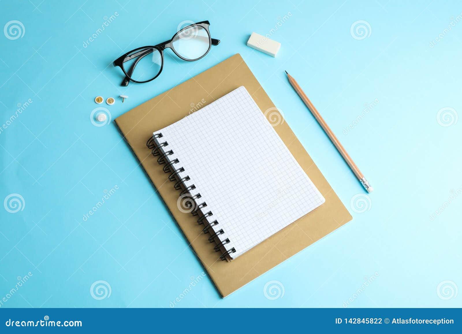 Тетради с прописями, карандаш и стекла на предпосылке цвета