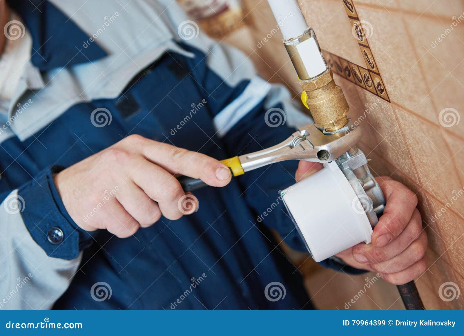 Техник водопроводчика работает с газовым счетчиком
