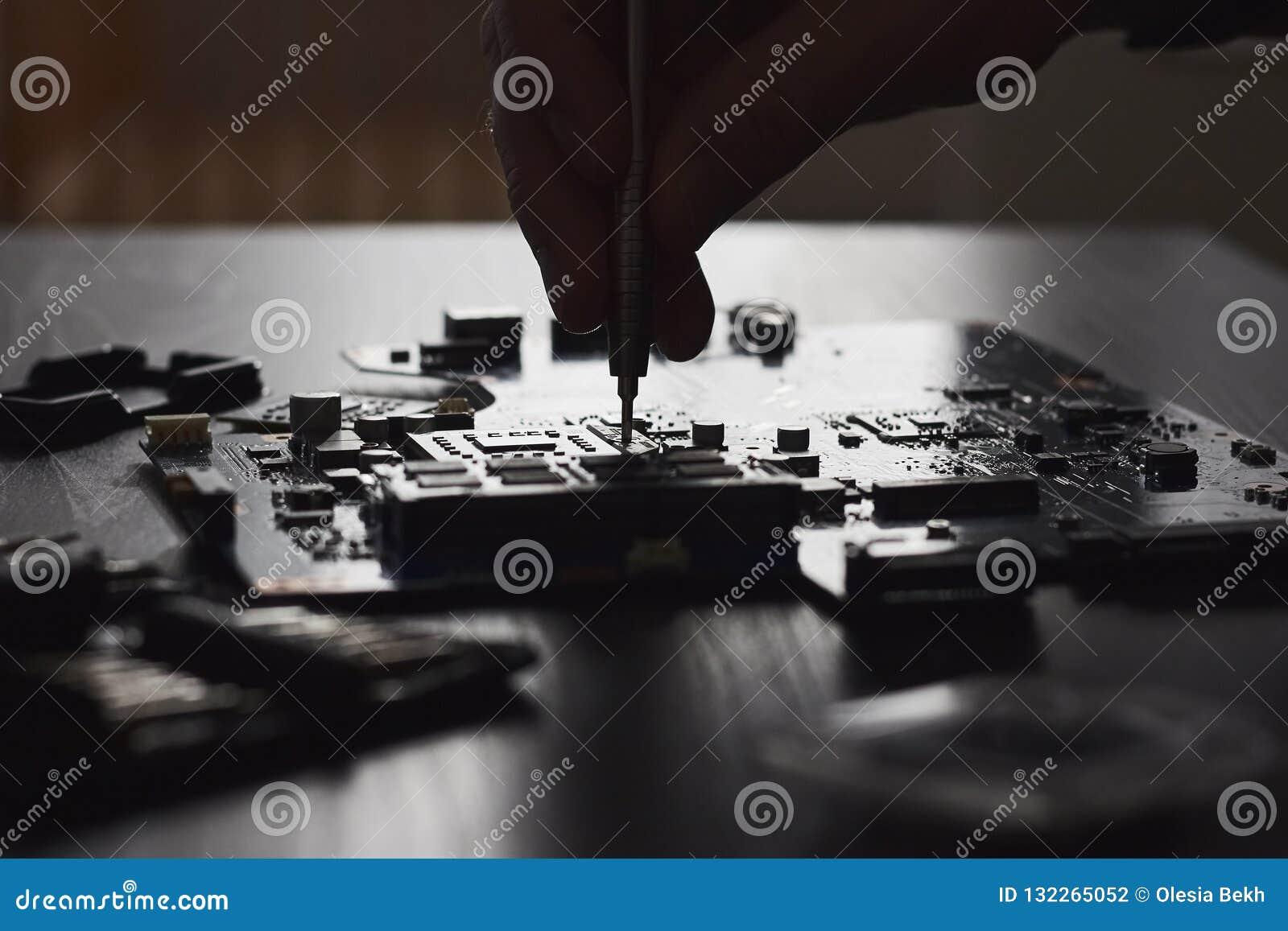 Техник затыкает внутри микропроцессор C.P.U. к материнской плате компьютера