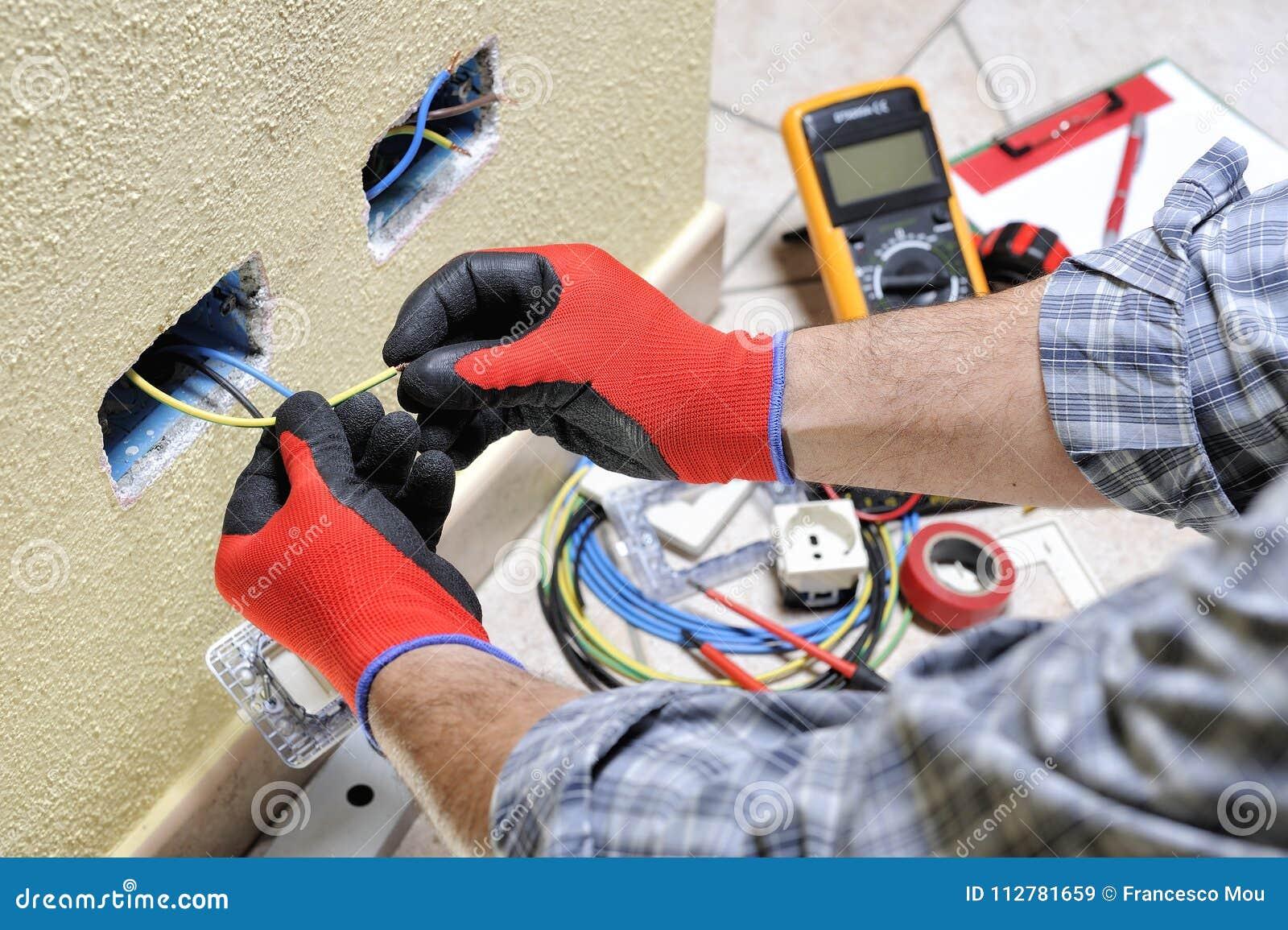 Техник электрика на работе с оборудованием для обеспечения безопасности на жилой электрической системе