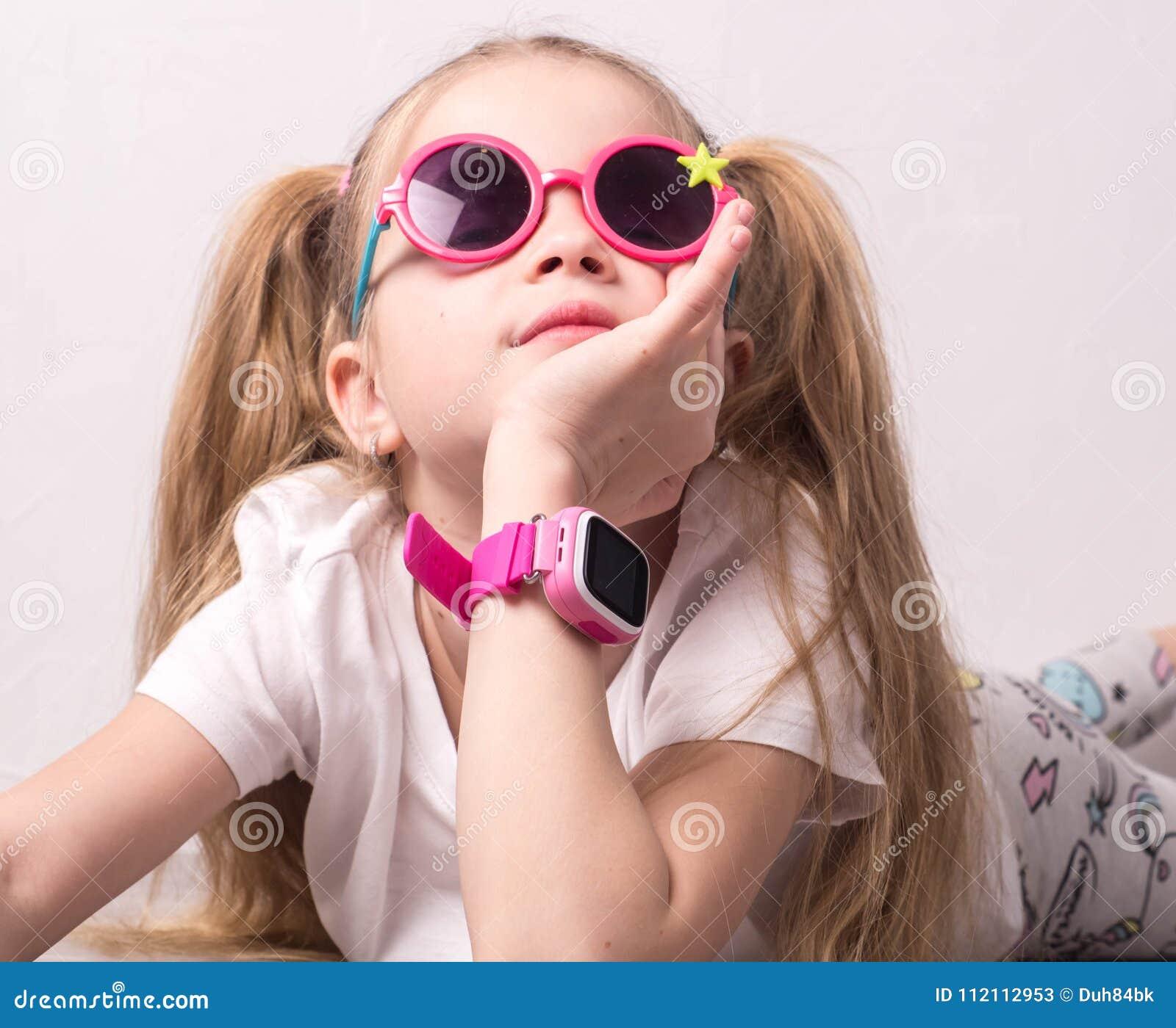 Технология для детей: девушка нося розовые стекла использует smartwatch